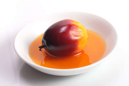 cooking oil: Fresh oil palm fruit and cooking oil on white plate