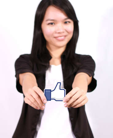 Johor, Malaysia - July 29, 2013  A woman hand holding like icon  This icon button is the voting system used to rate user comments on Facebook
