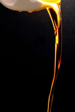 close up of gold and fresh cooking oil on black background