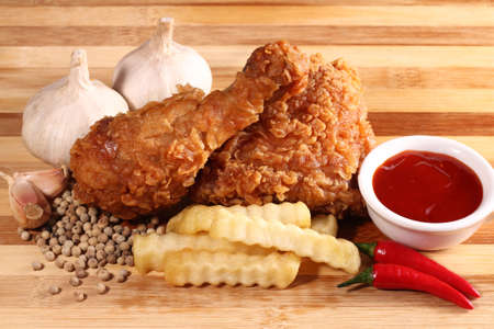 Hot and crispy fried chicken, french fries, chili, garlic and black pepper photo