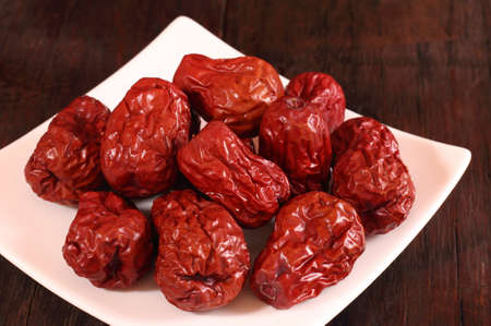 jujube fruits: Dried chinese jujubes fruits with white plate on wooden table