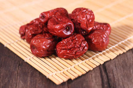 Dried chinese jujubes fruits with bamboo mat on wooden table photo