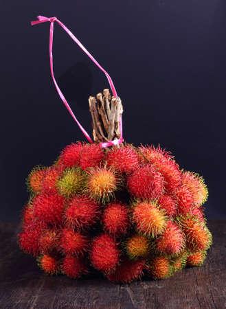 rambutan: A bunch of fresh red rambutan fruits on wooden table
