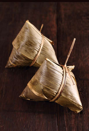 Two traditional homemade chinese rice dumplings on brown color background