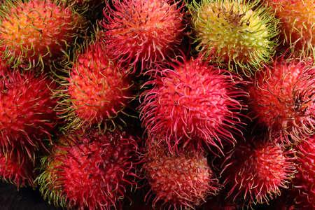 rambutan: A bunch of fresh red rambutan fruits on black background