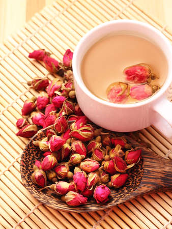 Dried roses, wooden scoop and a cup of rose tea on bamboo mat Banque d'images