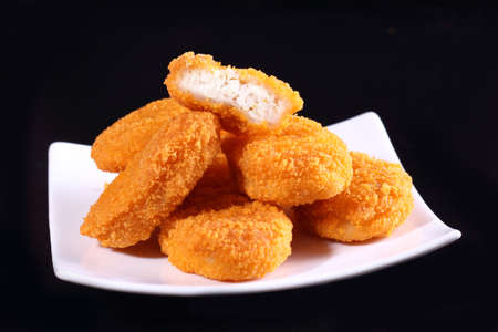 A pile of chicken nuggets on white plate with black color background