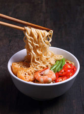 Hot and spicy instant noodle isolated on the dark color background photo