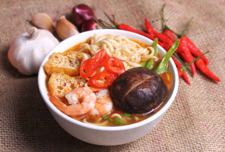 instant noodle: Hot and spicy instant noodle and ingredients on the sack background Stock Photo
