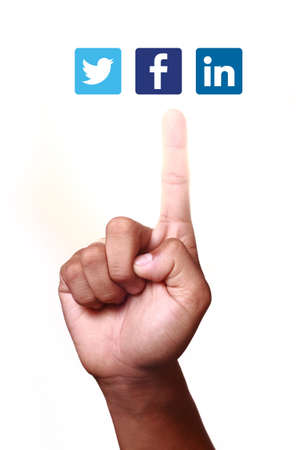 Johor, Malaysia - May 11, 2014  Index finger pointing at social networking icons  They are famous social networking websites, May 11, 2014 in Johor, Malaysia