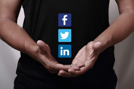 linkedin: Johor, Malaysia - May 11, 2014  Hand showing Facebook, Twitter and Linkedin icons  They are famous social networking websites in the world, May 11, 2014 in Johor, Malaysia