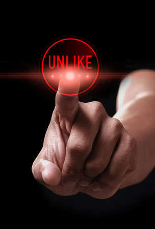 unlike: Hand pressing unlike icon on a virtual screen Stock Photo