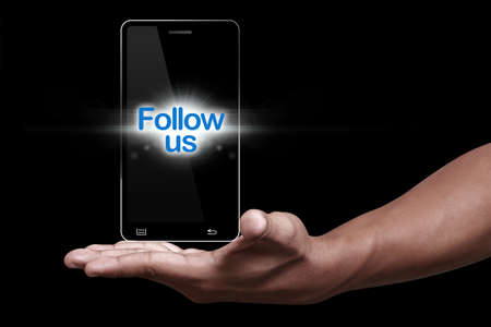 follow us: Hand showing smartphone with follow us icon