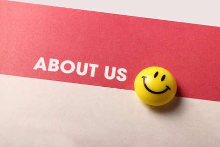 About us and smiley icon isolated on brown background