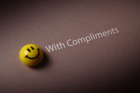 respecting: with compliments and smiley icon isolated on brown background