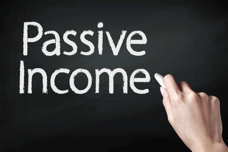 passive income: Hand writing passive income with white chalk Stock Photo