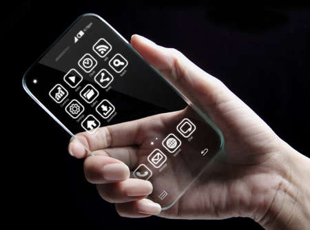 promising: Hand and futuristic transparent smartphone isolated on black background. The most promising technologies in the mobile market is flexible and transparent displays.
