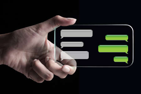 conveys: Hand showing chat bubbles on transparent 3D smartphone with black background. A 3D phone is a mobile phone that conveys depth perception to the viewer by employing stereoscopy or any other form of 3D depth techniques. Stock Photo