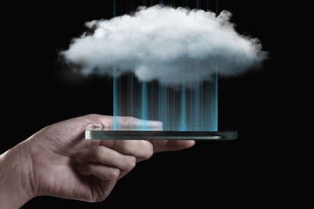 Cloud computing technology with hand and smartphone isolated on black background. Cloud computing is a general term for the delivery of hosted services over the Internet.