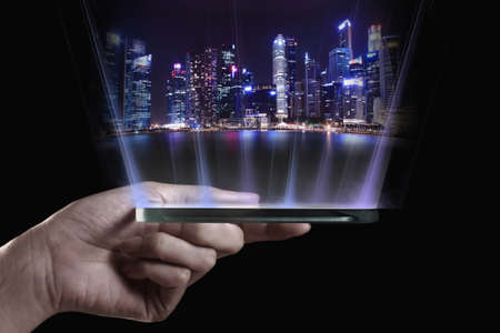 Hand holding transparent 3D smartphone. A 3D phone is a mobile phone that conveys depth perception to the viewer by employing stereoscopy or any other form of 3D depth techniques. Standard-Bild