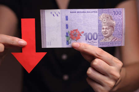 depreciation: Malaysian Ringgit with a red arrow to imply the fall or devaluation of Malaysian ringgit currencies.