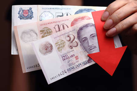 imply: Singapore dollar with a red arrow to imply the fall or devaluation of Singapore dollar currencies.