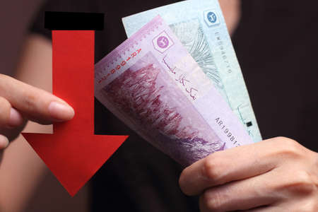 devaluation: Malaysian Ringgit with a red arrow to imply the fall or devaluation of Malaysian ringgit currencies.
