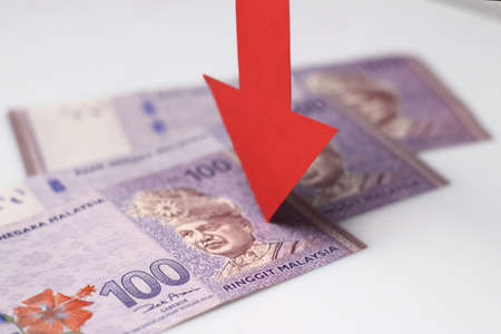 Malaysian Ringgit with a red arrow to imply the fall or devaluation of Malaysian ringgit currencies.