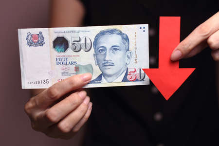 devaluation: Singapore dollar with a red arrow to imply the fall or devaluation of Singapore dollar currencies.