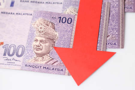 imply: Malaysian Ringgit with a red arrow to imply the fall or devaluation of Malaysian ringgit currencies.