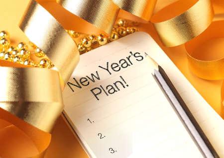 New Year: Plan ze złotymi ozdobami koloru noworoczny. Plan noworoczne są uchwałami albo obiecuje, że ludzie robią na Nowy Rok, aby ich nadchodzący rok lepiej w jakiś sposób.