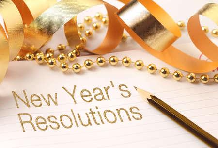 metas: Resoluciones de a�o nuevo con decoraciones de color oro. Las resoluciones de A�o Nuevo son metas o promesas que la gente hace para el A�o Nuevo para hacer su pr�ximo a�o mejor de alguna manera. Foto de archivo