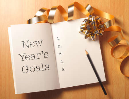 new: New Years goals with gold color decorations. New Year's goals are resolutions or promises that people make for the New Year to make their upcoming year better in some way. Stock Photo
