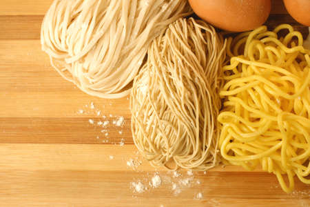 Handmade noodles and ingredients on chopping block. Noodles are an essential ingredient and staple in Chinese cuisine. Stock Photo