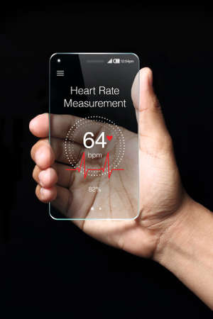 mobile phones: Transparent smartphone, heart rate measurement application with hand on dark background.