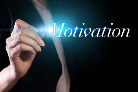 motivation: Hand writing motivation on virtual screen Stock Photo