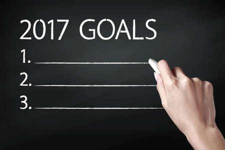 metas: Mano que sostiene una tiza y escribir metas 2017