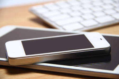 easier: Smartphone, tablet and keyboard on wooden table background. Smartphone and tablet have made our life easier. Stock Photo