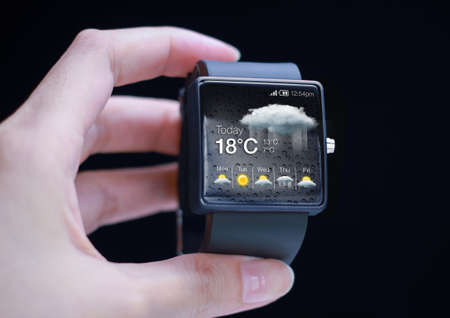 innovating: Smartwatch with weather icon in hand. Weather forecasting is the application of science and technology to predict the state of the atmosphere for a given location.