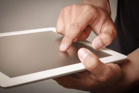 business tool: Hand touching a tablet. Tablets are a powerful tool for enhancing your productivity and online experience whether for business use, or life in general.