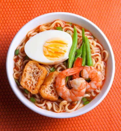 comida: Fideos instantáneos calientes y picantes aislados en el fondo de color naranja