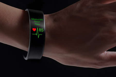rate: Measurate heart rate application with smart wristband. A smart wristband is a wearable computing device that closely resembles a wrist watch or other time-keeping device. Stock Photo