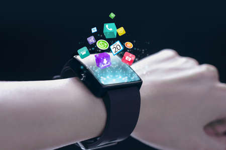 timekeeping: App icons with smartwatch. A smartwatch is a wearable computing device that closely resembles a wristwatch or other time-keeping device.