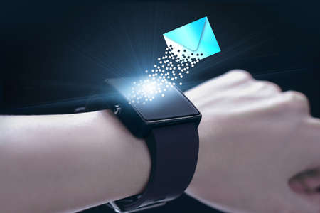 timekeeping: New message icon with smartwatch. A smartwatch is a wearable computing device that closely resembles a wristwatch or other time-keeping device. Stock Photo
