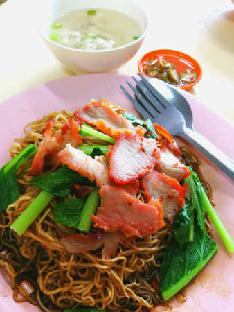 Wonton noodles is a Cantonese noodle dish which is popular in asia. The dish is usually served in a hot broth, garnished with leafy vegetables, and wonton dumplings.  Stock Photo