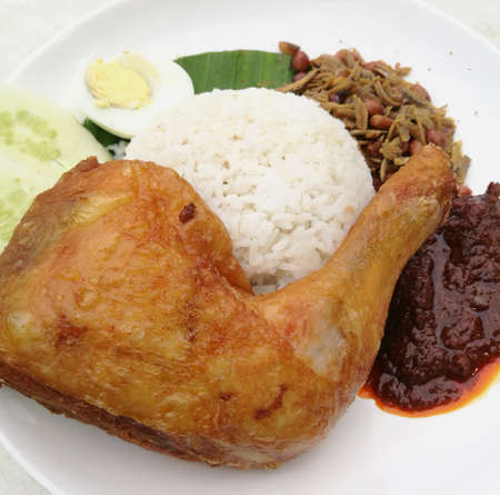 Nasi lemak is a Malay fragrant rice dish cooked in coconut milk and pandan leaf. Stock Photo