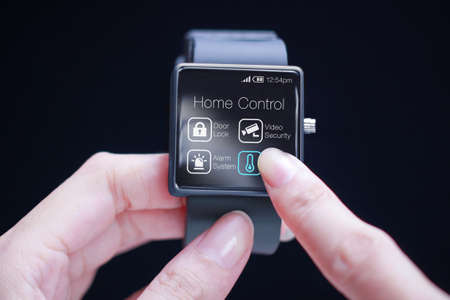 Hand touching home control application on smartwatch. Home automation is the use and control of home appliances remotely or automatically.