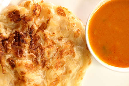 Roti Canai is a soft bread made by tossing and spinning the dough. This popular Malaysian dish. Stock Photo