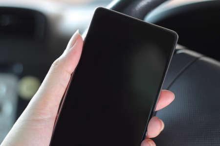 easier: Mobile smart phone with blank screen in car. Smartphones make driving easier.