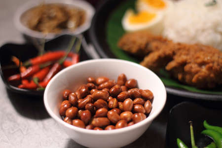 popular: Nasi lemak is served with a hot spicy sauce, cucumber slices, small fried anchovies, roasted peanuts, and hard-boiled or fried egg.